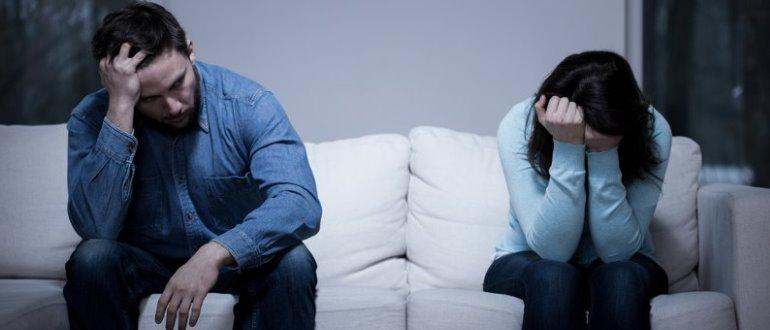 Мужчина и женщина грустят на диване