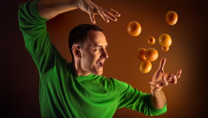 Мужчина жонглирует апельсинами