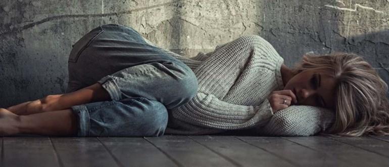 Девушка лежит на полу в свитере