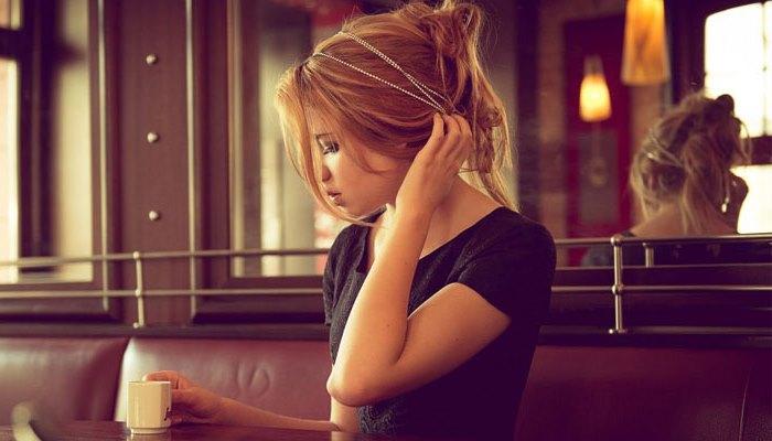 Девушка поправляет прическу в кафе