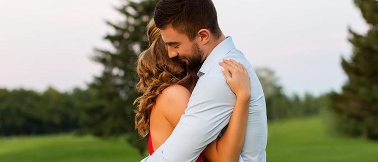 Нежно обнимает девушку